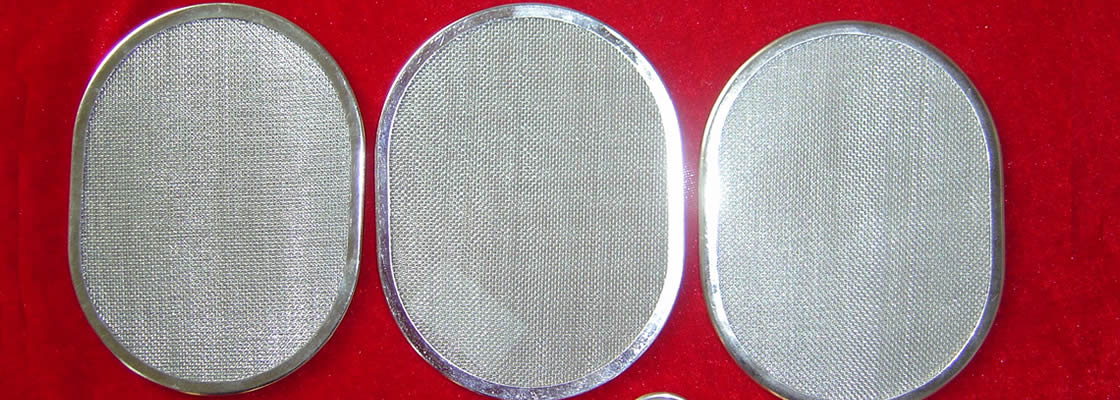 Three oval shaped filter discs with stainless steel metal gaskets and stainless steel wire meshes are on the red cloth.