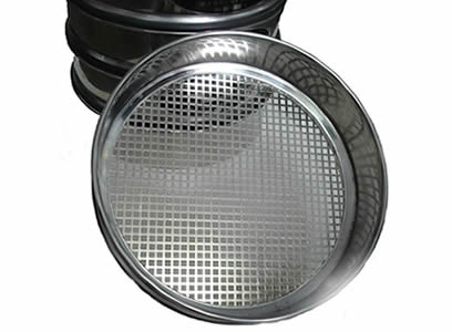 A stainless steel perforated test sieve lean on a stack of test sieves, and its hole shape is square.